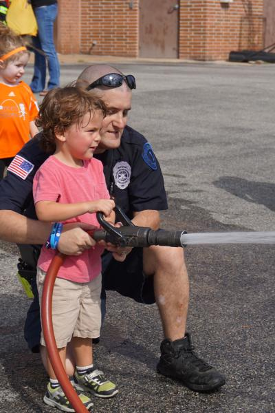 Future firefighter Christopher practicing hose handling with firefighter Gauge
