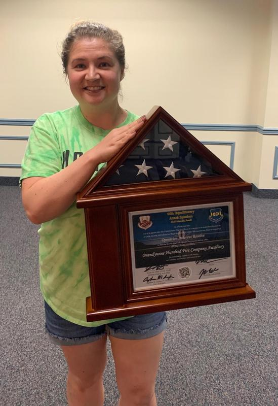 Heather holding the U.S. Flag / Certificate presented to BHFC.